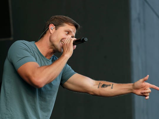 Country singer Walker Hayes gestures toward the crowd, revealing a new tattoo of his late daughter's footprint, during his show at the U.S. Cellular Connection Stage at Summerfest Wednesday night.