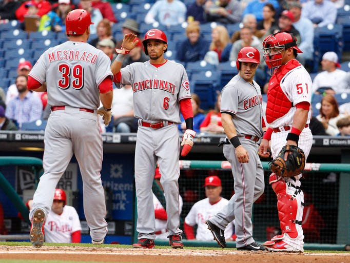 Cincinnati Reds' Devin Mesoraco, left, comes home after hitting a three-run home run scoring, Billy Hamilton, center left, and Skip Schumaker, center right, as Philadelphia Phillies' Carlos Ruiz, right, watches.