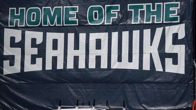 A UNCW sign hangs from the E. Marvin Johnson Training Facility next to Brooks Field.