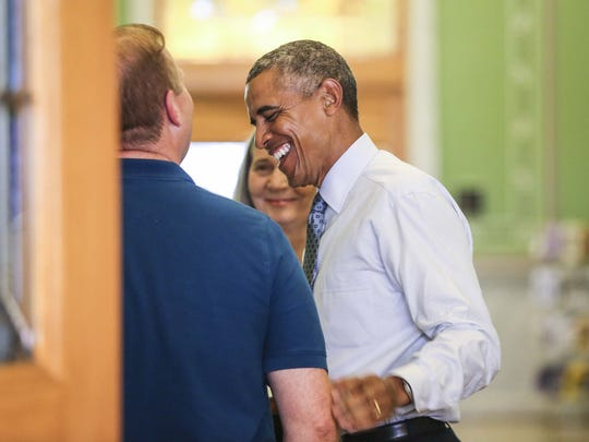 President Barack Obama laughs with State Librarian Michael Scott at the State Library in Des Moines, Iowa, Monday Sept. 14, 2015.
