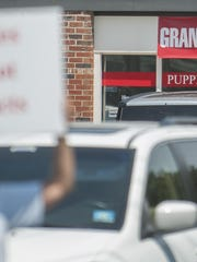 """Animal right activists protest outside of Pat's Pups, a new pet store located in Saw Mill Village shopping center on Route 70 in Cherry Hill. The activist believe that the store is getting the puppies it sells from so-called """"puppy mills,"""" establishments that breed puppies in inhumane conditions for sale. 08.06.15"""