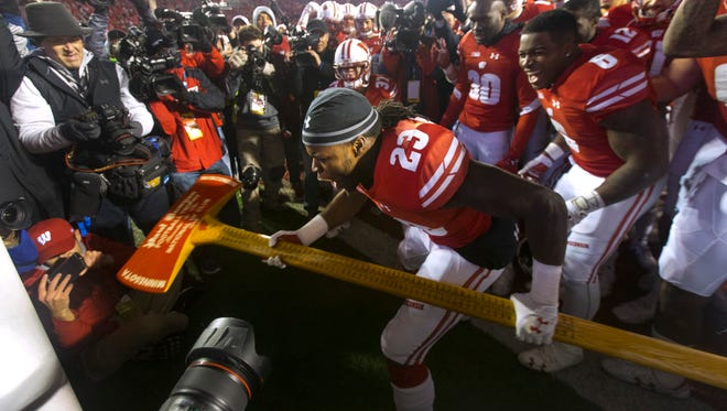 "Wisconsin running back Dare Ogunbowale celebrates by ""chopping down a  goal post"" with Paul Bunyan's Axe."