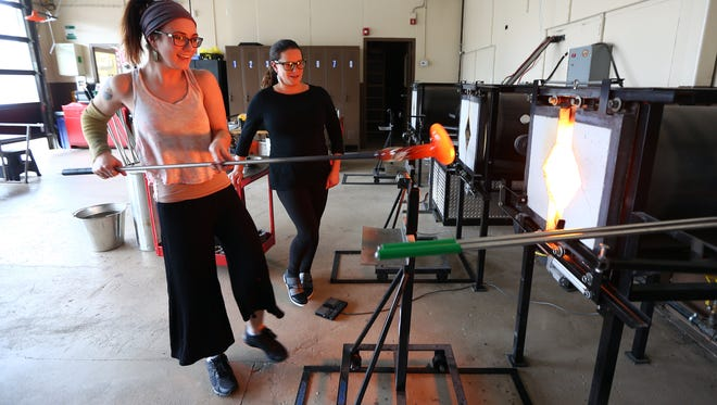 Lead instructor Hannah Muller pulls  the piece from the furnace as studio manager/program coordinator Michelle Knox  looks on at the Morris County School of Glass, a public access glass blowing school for students of all ages. February 15, 2018. Morristown, NJ.
