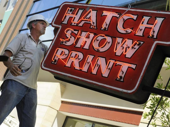 David Hampton of Joslin Signs tests the neon before hanging the Hatch Show Print sign on its new home, the Country Music Hall of Fame and Musuem, in 2013. At Hatch Show Print, you can get a 130-year look at posters that have sold millions of tickets for thousands of artists.