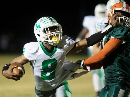Fort Myers High School's Willie Neal is tackled by
