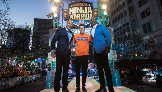 """IndyCar driver Scott Dixon, middle, poses with """"American Ninja Warrior"""" hosts Matt Iseman, left and Akbar Gbaja-Biamila, right, before his attempt on the course Sunday in Downtown Indy."""