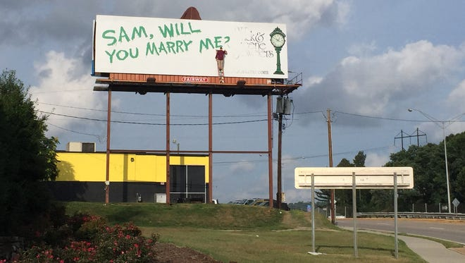 What looks like a man painting a marriage proposal on a billboard is actually a piece of creative advertising by Wick and Greene Jewelers, a downtown Asheville jewelry store.
