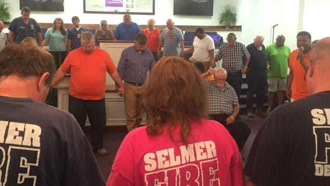 A group prays at a critical incident debriefing Monday in Selmer.