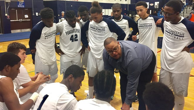 Coach Jerome Elting huddles his Poughkeepsie High School boys basketball team during a game on Friday.