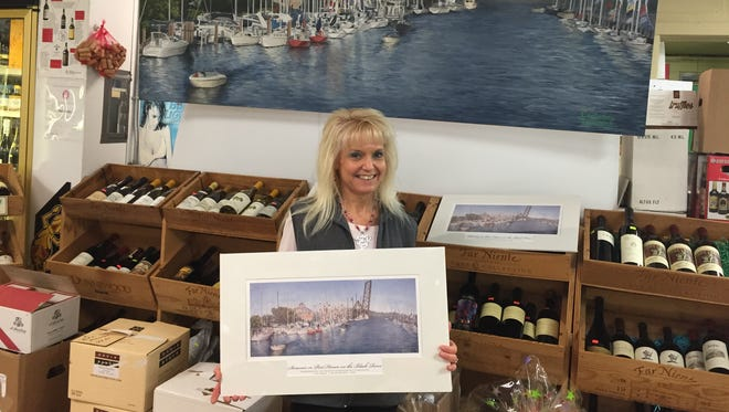 Trina Kern-Avedisian holds a print of the larger painting behind her. The Art on the River committee is selling the prints and auctioning the painting to raise money for the 2017 event.