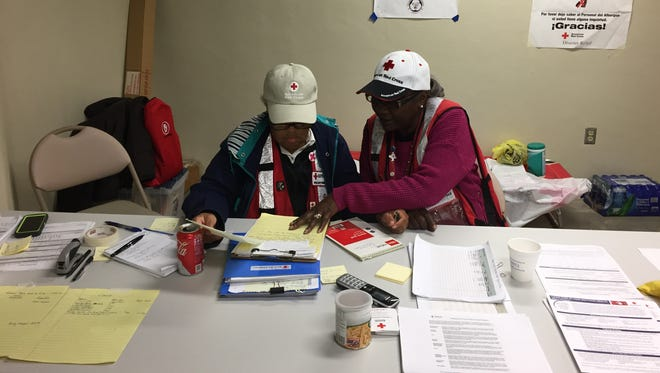 Bonnie Edwards, left, an American Red Cross volunteer, goes over the list of Forrest County 361 Shelter residents with another volunteer.