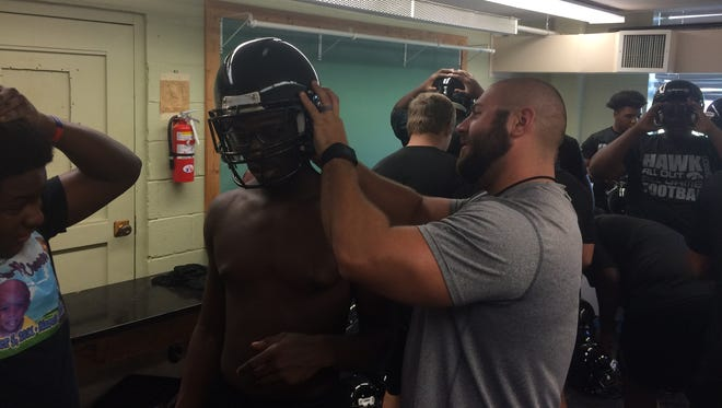 South Side coach Tyler Reeder helps a player find a helmet that fits him before practice on July 10, 2017..