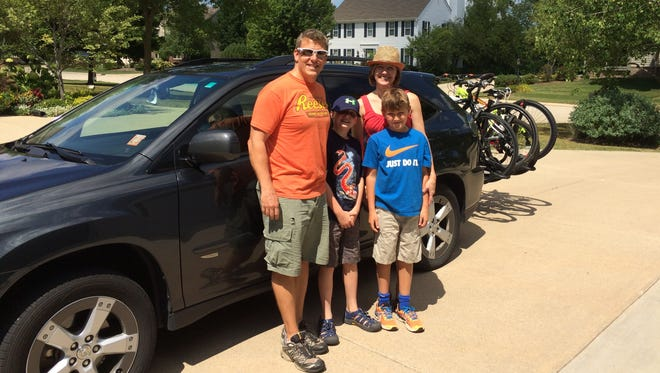 Richard Ratay and his family pose in front of their road trip vehicle.
