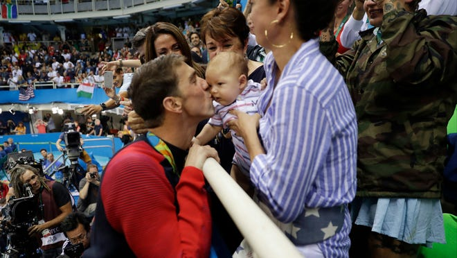 Michael Phelps kisses his son, Boomer, during the Rio Olympics.