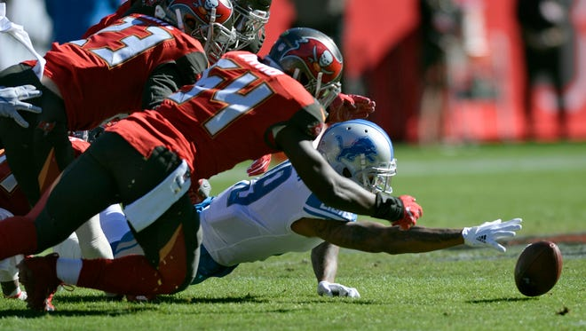 Lions wide receiver Kenny Golladay, bottom, and Buccaneers outside linebacker Lavonte David (54) and free safety Chris Conte go for a fumble by the Lions' Eric Ebron during the first half of the Lions' 24-21 win on Sunday, Dec. 10, 2017, in Tampa, Fla.