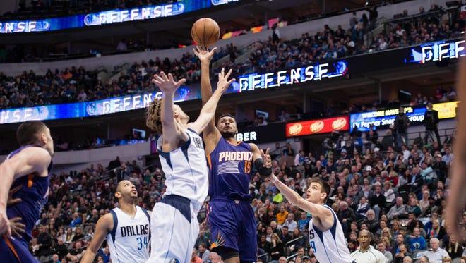 Jan 5, 2017; Dallas, TX, USA; Phoenix Suns guard Leandro Barbosa (19) shoots over Dallas Mavericks forward Dirk Nowitzki (41) and forward Nicolas Brussino (9) during the second quarter at the American Airlines Center.