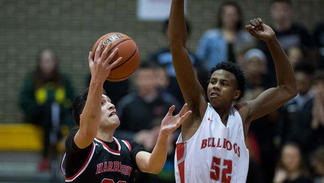 Harrison's Robin Duncan (20) shoots against Bosse's Kiyron Powell (52) during the SIAC Championship game at Central High School Saturday night. Bosse beat Harrison 106-63.