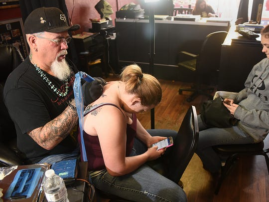 Greg Knuppel, left, creates a tattoo for Brittany Rodgers, center, while Rodgers' friend, Ashley Ortega, waits during Small Business Saturday on Saturday at Mr. Tank's Tattoos in downtown Farmington.