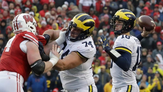 Michigan quarterback Brandon Peters throws during the first half against Wisconsin, Saturday, Nov. 18, 2017 in Madison, Wis.