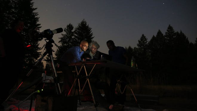 Andrew Jozwiak (left) and Richard Berry look at a monitor as images appear from the nearby telescope while working in Lyons, Oregon, on Monday, Aug. 7, 2017.