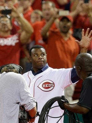 Former Cincinnati Reds star Ken Griffey Jr. waves to the crowd as he is introduced following a baseball game between the Reds and the Miami Marlins, Friday, Aug. 8, 2014, in Cincinnati. Griffey will be inducted into the Reds hall of fame Saturday. (AP Photo/Al Behrman)