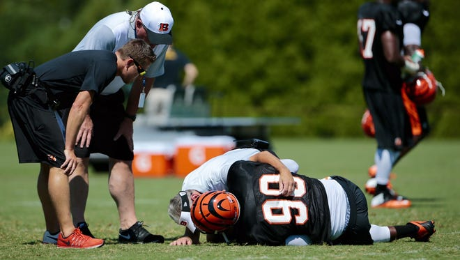 Michael Johnson holds his right knee after going down during practice.