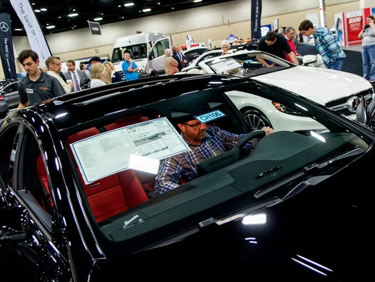 A visitor checks out a Mercedes-Benz AMG CLS63 S Coupe at the annual Knoxville News Sentinel Auto Show at the Knoxville Convention Center on Saturday, February 25, 2017.