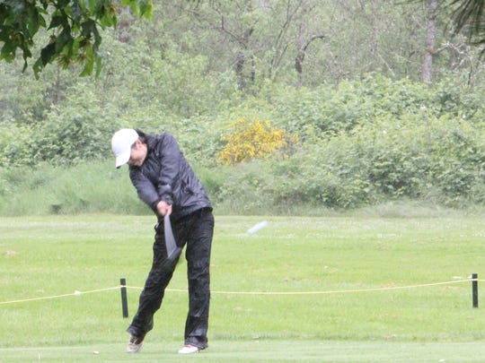 South Salem junior Ashley Zhu tees off in the driving rain at the OSAA Class 6A state golf tournament on Tuesday, May 16, 2017.