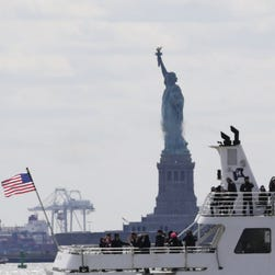 A tourist boat sails past the Statue of Liberty in New York, 2015.