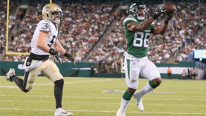 Aug 24, 2019; East Rutherford, NJ, USA; New York Jets running back Ty Montgomery (88) catches a touchdown pass as New Orleans Saints linebacker Colton Jumper (51) defends during the first half at MetLife Stadium. Mandatory Credit: Vincent Carchietta-USA TODAY Sports