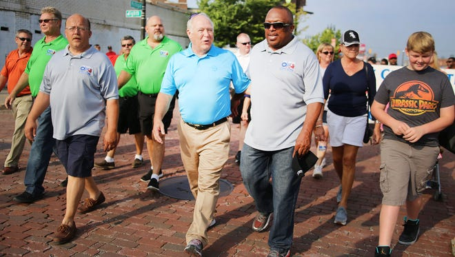 Dennis Williams, UAW President , center left in blue,  chats with Chuck Hall, UAW Region 1 director, as they march in Detroit's annual Labor Day Parade along Michigan Ave. in Corktown Monday, Sept. 7, 2015 heading for downtown Detroit.