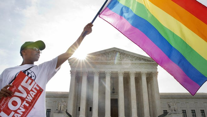Carlos McKnight of Washington, waves a flag in support of gay marriage outside of the Supreme Court in Washington D.C. on Friday June 26, 2015. The 5-4 opinion supporting gay marriage was among the remaining to be released before the term ends at the end of June.