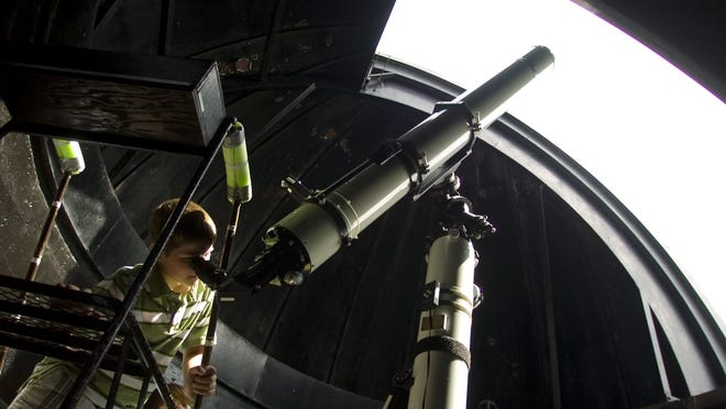 A student peers through a telescope fitted with a solar filter to view the sun at Kopernik Observatory and Science Education Center in Vestal in this 2010 photo.