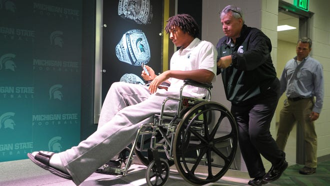 Michigan State redshirt freshman safety Jalen Watts-Jackson, who made the winning fumble recovery and touchdown against Michigan, is wheeled into the press conference Tuesday.