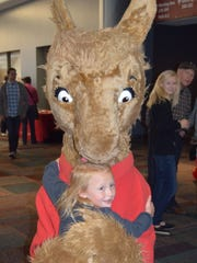 Kenwood resident Claire Anders gets a hug from children''s book character Llama Llama during the 2014 Books by the Banks at the Duke Energy Convention Center. The event returns this weekend.