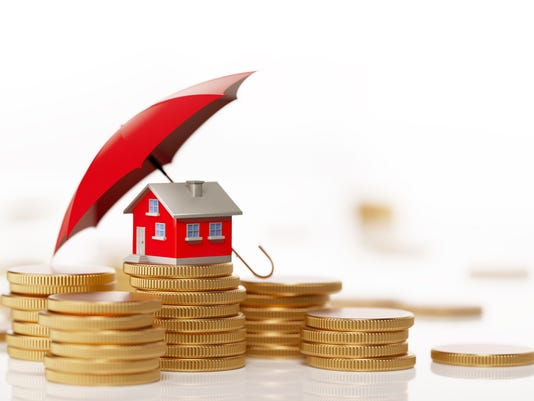 Red Toy House Sitting On White Background Behind Coin Stack: Insurance And Real Estate Concept