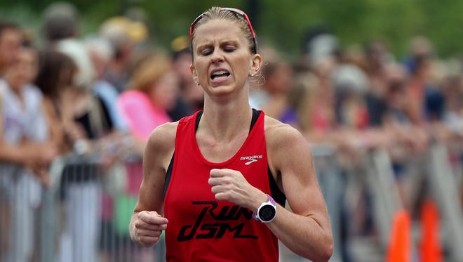 Ellen Ries, 27 of Des Moines, a North Linn High School and Missouri graduate, hit the finish line in the Dam To Dam half marathon women's race in downtown Des Moines on Saturday morning May 31, 2014.