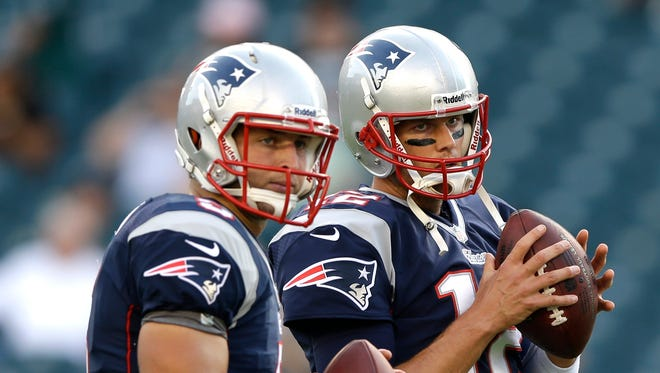 im Tebow, left, and Tom Brady warm up before a preseason NFL football game in 2013.