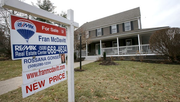 A for sale sign stands in front of a house, in Walpole,