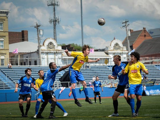 The Saints compete against Buffalo FC last year at Taft High School. Downtown and Music Hall can be seen in the background.