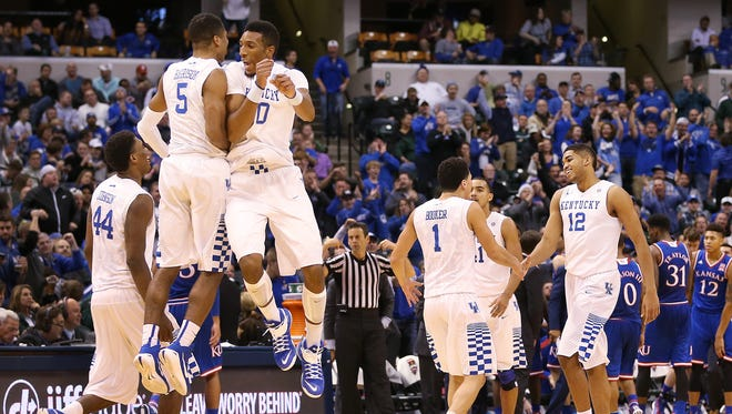 Kentucky Wildcats guard Andrew Harrison and forward Marcus Lee go airborne to celebrate a big lead over Kansas in the second half at Bankers Life Fieldhouse Tuesday, Nov. 18, 2014.
