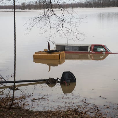 A truck is nearly fully submerged in flood water in