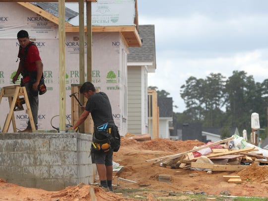 Construction crews work on single family homes, where 35 have already been completed, in the Canopy Development within Welaunee on Friday, July 6, 2018.