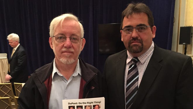 John Morawetz (left), of the International Chemical Workers Union Council, and Roy Reed, a DuPont employee in LaPorte, Texas, show a sign with photos of the four workers killed at the LaPorte plant in 2014. They were attending DuPont's annual meeting at the Lotte New York Palace Hotel on Wednesday. Safety of workers was discussed at length during the meeting.