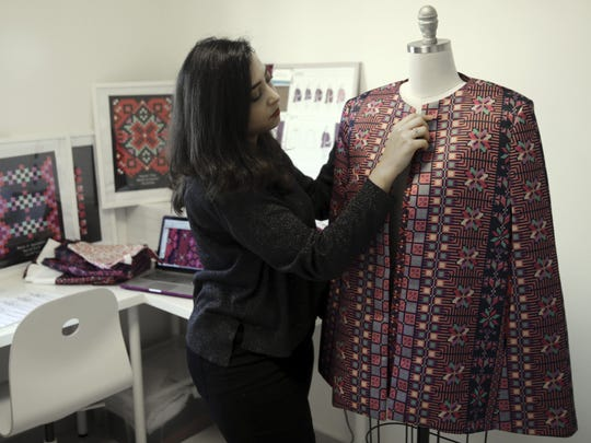 In this Tuesday, Jan. 29, 2019 photo, designer Natalie Tahhan works on a modern version of the traditional Palestinian thobe in her studio in east Jerusalem.