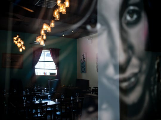 The dining area of Kitchen 519 restaurant is seen reflected in a piece of artwork, Thursday, August 7, 2014 in Glendora.