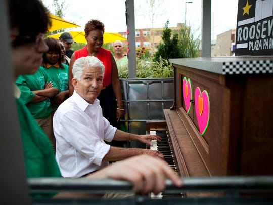 Resident Christopher Andrew Maier plays a piano after the unveiling of a pop-up park at Roosevelt Plaza Park, Monday, September 8, 2014 in Camden.