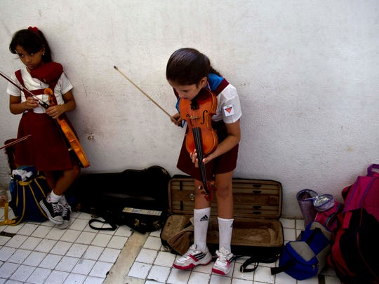 First year violin students wait on Oct. 9 to play individually during class at the Manuel Saumell music school in Havana, Cuba. Cuba's dozens of free music schools turn out thousands of skilled young musicians each year, many of whom play imported instruments that can only be repaired and maintained with hard-to-find materials from abroad.