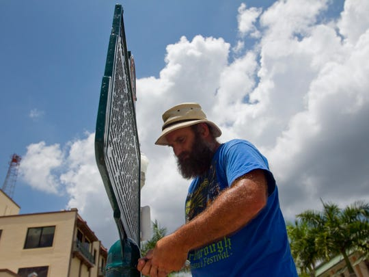 Vale Fillmon installs the refurbished historical marker for the battle of Fort Myers in front of the new downtown library on Friday. Fillmon hand painted all of the text on the marker.