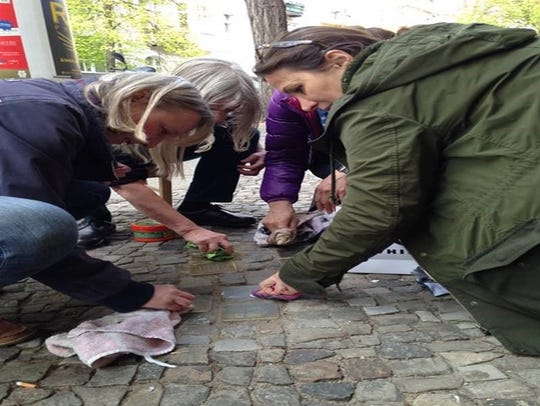 Residents of Berlin's Tiergarten district polish  stolpersteine,